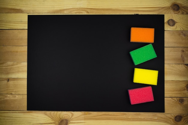 New multi-colored foam sponges on a black background