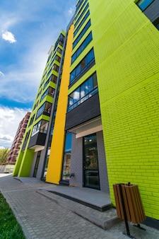 Новый многоэтажный жилой дом цвета кирпича на фоне голубого неба с солнечными бликами