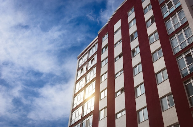 Новое многоэтажное здание на фоне неба, в окнах которого отражается солнце