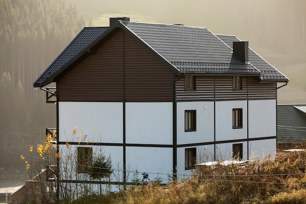New nice white and brown two-storied cottage with shingle roof in ecological area on foggy wood and hills on sunny summer day. well maintained property, real estate concept.