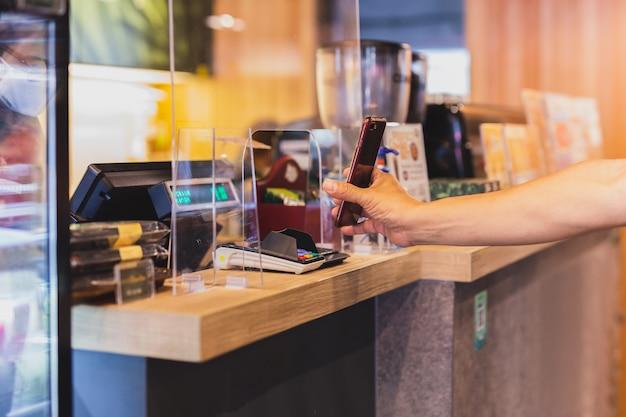 カフェでプラスチック製のパーティションを隠したスタッフと携帯電話で請求書を支払う新しいnomarlの顧客。
