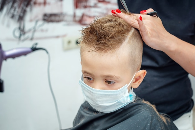 New normal adapting to normal life after pandemic lockdown. boy getting hair cut wearing mask.