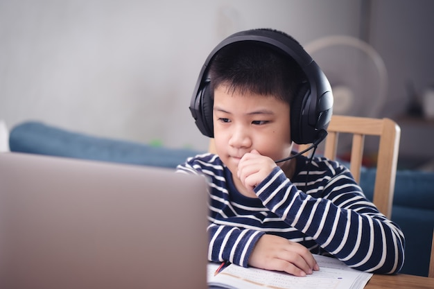 New normal asian boy study online looking at the screen laptop happy smile and laugh with fun at home. technology education concept, work from home