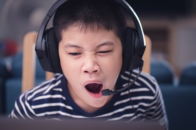 New normal asian children study online, look at the laptop screen feeling sleepy with exhaustion and boredom at home technology education concept work from home