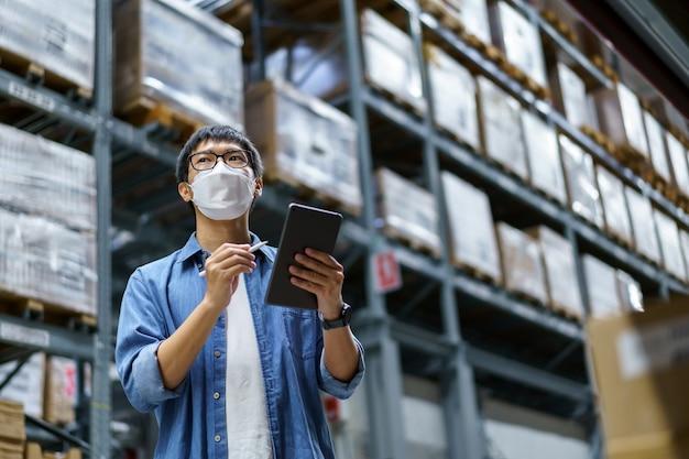 Новые нормальные азиатские мужчины, персонал, продукт в маске для лица. счетчик менеджер по контролю за складом стоянка, подсчет и проверка товаров на складе