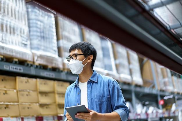 新しい通常のアジア人男性、スタッフ、フェイスマスクを着用した製品。倉庫管理マネージャーのカウント倉庫内の製品の立ち、カウント、検査