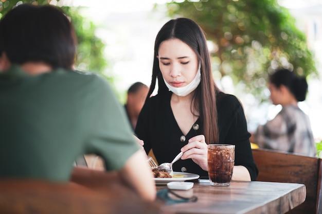 식당에서 먹는 새로운 일반 아시아 여성 얼굴 마스크 프리미엄 사진