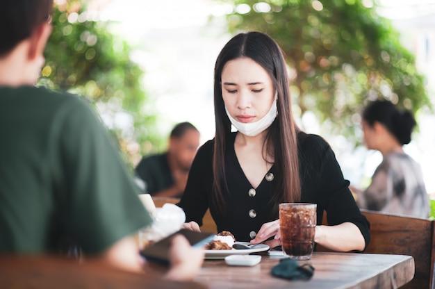 식당에서 먹는 새로운 일반 아시아 여성 얼굴 마스크