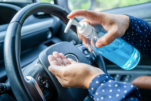 プレスブルーアルコール消毒ジェルで手を洗う新しい通常のアジアの働く女性