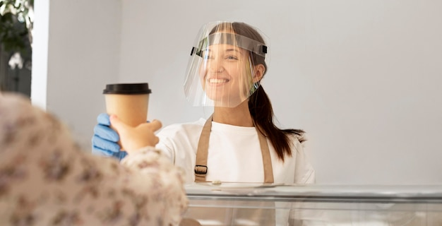 フェイスシールド付きのコーヒーショップでの新しい通常