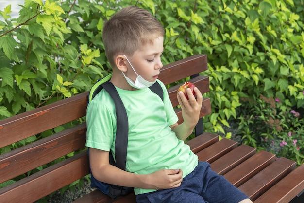 Новый нормальный, снова в школу. школьник в медицинской маске и рюкзаке обедает на скамейке во время перемены
