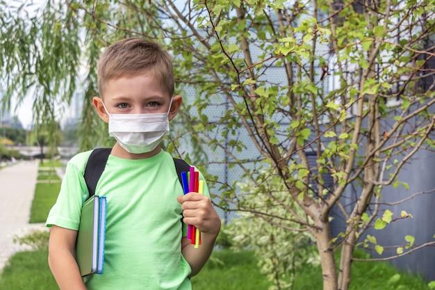 Новый нормальный, снова в школу. школьник в медицинской маске и рюкзаке с учебником и фломастерами на открытом воздухе