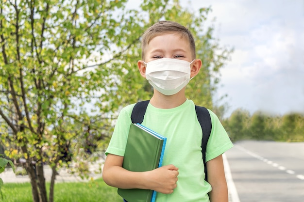 新しい通常、学校に戻って。医療マスクと屋外で教科書を保持しているバックパックを身に着けている少年