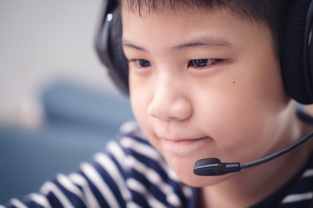 New normal closeup faces asian boy study online looking at the screen laptop happy smile and laugh with fun at home. technology education concept, work from home