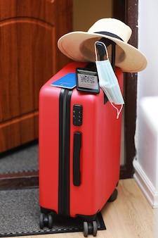 뉴노멀 컨셉. 면역 디지털 건강 여권, 빨간 여행 가방, 보호 마스크, 밀짚 모자, 여권, 선글라스가 있는 스마트폰을 가까이서 보세요. 전염병 동안 비행기로 여행.