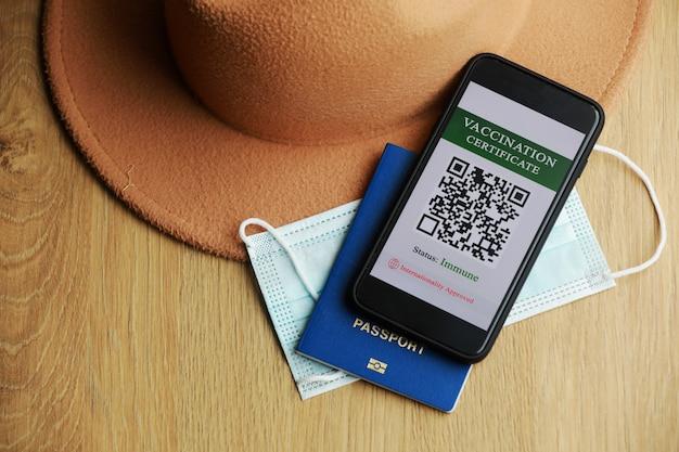 Новая нормальная концепция. крупным планом вид смартфона с иммунным цифровым паспортом здоровья. на деревянном фоне защитная маска, шапка и паспорт.