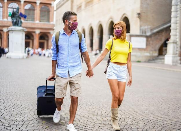 新しい通常のコンセプト。 covid-19から身を守るためにマスクを身に着けているカップルは、休暇中にスーツケースを持って街に歩いています。