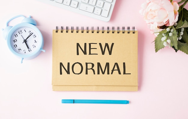 우리의 라이프 스타일을 사무실 책상에 노트북에 적힌 단어로 제시된 새로운 정상으로 바꾸는 코로나 19 코로나 바이러스에 의해 영향을받은 새로운 정상 개념.