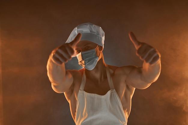 새로운 일반 개념. 연기가 자욱한 배경 남성 주부에 엄지를 보여주는 보호 의료 마스크 흰색 앞치마와 요리사 모자를 쓰고 근육 요리사의 초상화. 부엌에서 남편. 잔인한 정육점.
