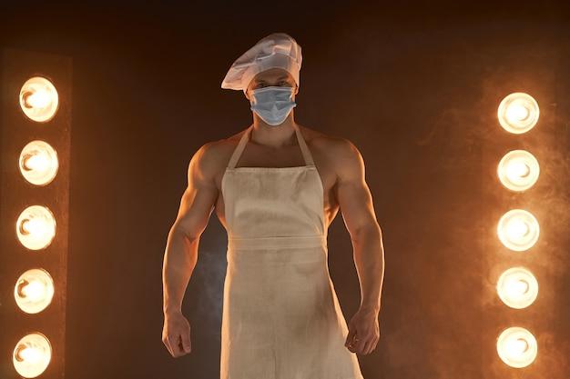 Новая нормальная концепция. портрет мускулистого шеф-повара, носящего защитную медицинскую маску, белый фартук и шляпу шеф-повара, стоя на дымчатом фоне и лампе света мужской домохозяйки. муж на кухне. жестокий мясник.
