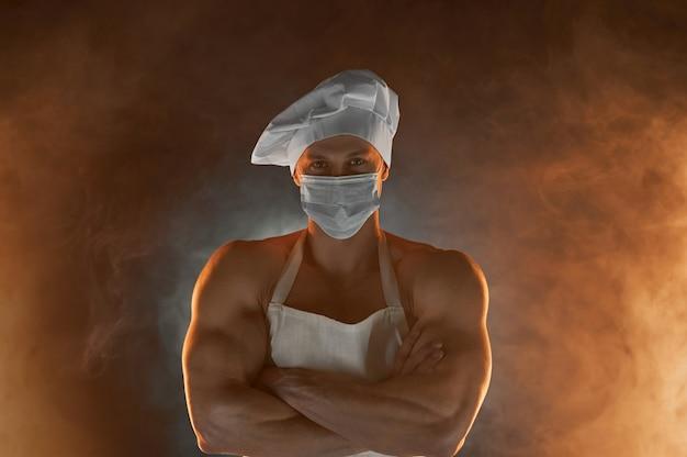 새로운 일반 개념. 보호 의료 마스크 흰색 앞치마와 요리사 모자를 쓰고 근육 요리사의 초상화