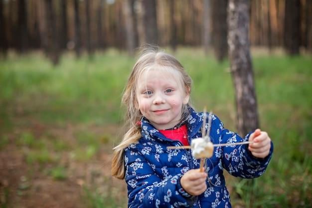 新しい通常の脱出ステップ、野生の自然のウォーキング、家族のアウトドアレクリエーション。火で揚げたマシュマロを調理して味わう子供たち、週末のハイキング、ライフスタイル