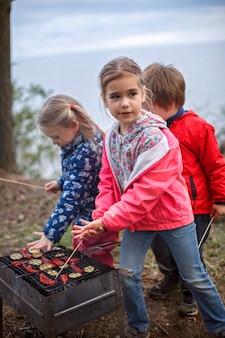 新しい通常の脱出ステップ、野生の自然のウォーキング、家族のアウトドアレクリエーション。親がチーズとソーセージを火で調理している間楽しんでいる子供たち、週末のハイキング、ライフスタイル