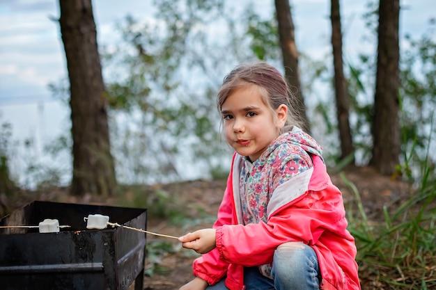 新しい通常の脱出ステップ、野生の自然のウォーキング、家族のアウトドアレクリエーション。火のそばに立ってマシュマロを調理する子供たち、週末のハイキング、ライフスタイル