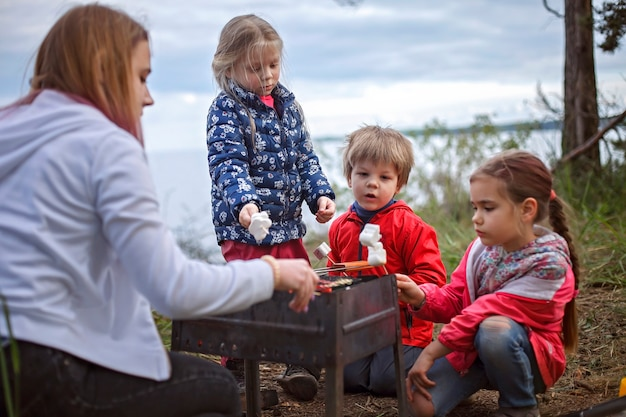 New normal escape step, wild nature walking and family outdoor recreation. kids standing by the fire and cooking marshmallows, hike at weekend, lifestyle