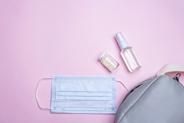 New normal. flat lay set of  women's handbag with medical face mask, sanitizer spray and pills. hygiene products