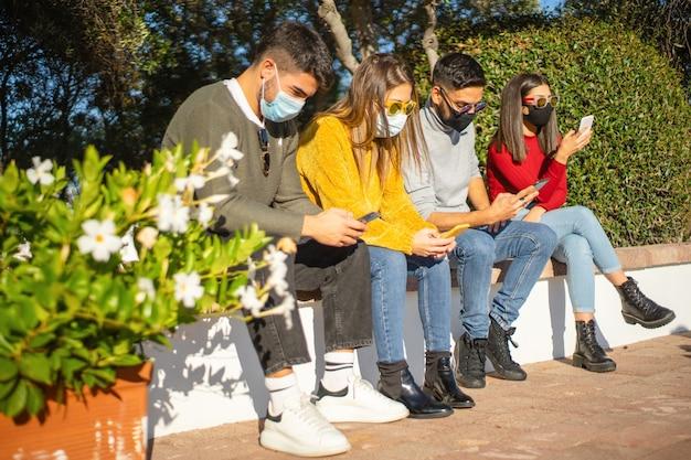 都市活動の人々の新しい常識:スマートフォンを使用し、コロナウイルスに対する保護マスクを着用している友人のグループ
