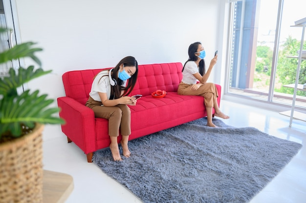 フェイスマスクと距離を保つことで新しい通常の生活。タイの友人と自宅でアジアの女性のライフスタイル。社会的距離と外出禁止令は安全を保ちます。