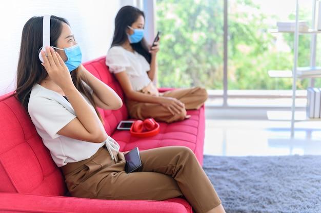 마스크를 쓰고 거리를 유지하는 새로운 일상. 태국 친구와 함께 집에서 아시아 여성의 생활 방식. 사회적 거리두기와 집에서 안전하게 지내세요.