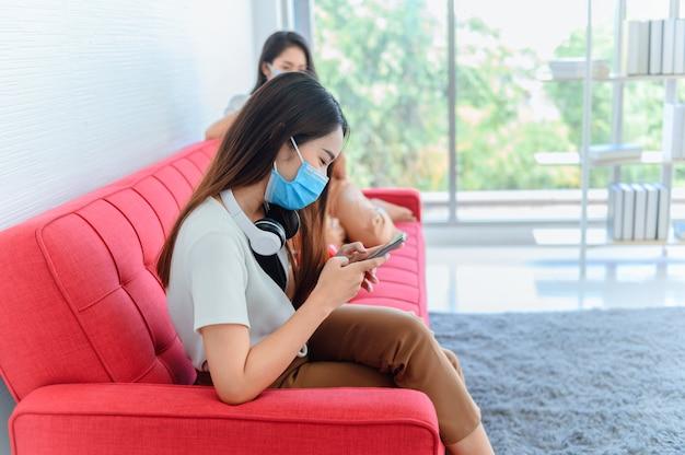 마스크를 쓰고 거리를 유지하는 새로운 일상. 태국 친구와 함께 집에서 아시아 여성의 생활 방식. 십대 휴식과 여름 집에서 레크리에이션.