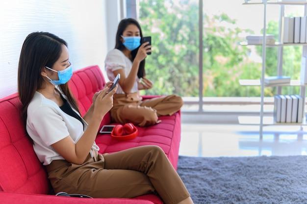 フェイスマスクと距離を保つことで新しい通常の生活。タイの友人と自宅でアジアの女性のライフスタイル。
