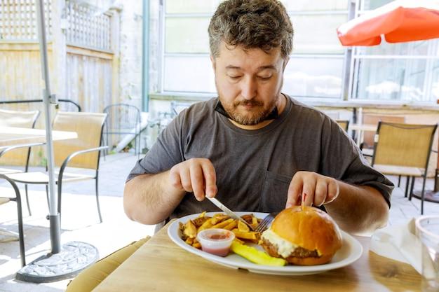 新しい通常の現実、ファーストフードレストランのストリートカフェで、屋外の食べ物で安全に滞在