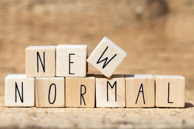 Новый обычный текст на деревянном кубе. новая нормальная жизнь после пандемии covid-19 с социальным дистанцированием и хорошей гигиеной на деревянном столе