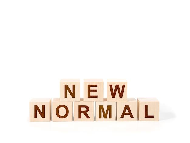 Новый обычный текст на деревянном кубе. белый фон. крупным планом. слово новый нормальный на деревянных кубиках на белом фоне.