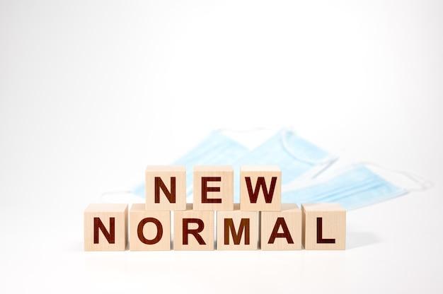 木製の立方体の新しい通常のテキスト。 newnormalワードの木製キューブ