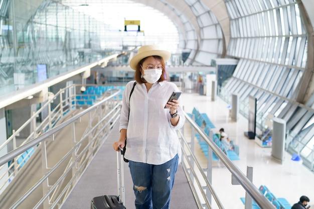 Новый нормальный турист в маске путешествует по аэропорту новый образ жизни путешествия после covid19