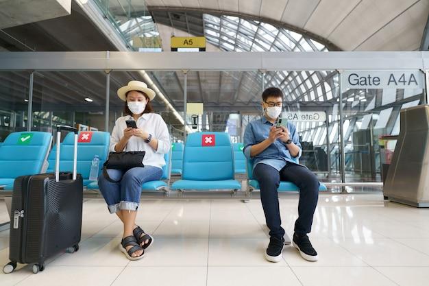 Новые нормальные туристы в масках путешествуют по аэропорту