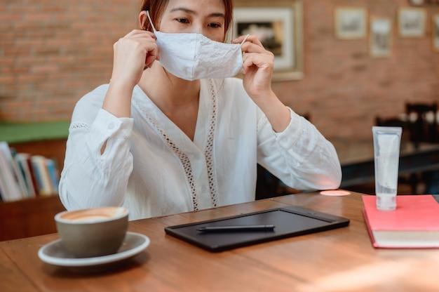 New normal с маской для лица и гелем для рук. азиатский образ жизни женщины в одиночку. работа в сети вне офиса.