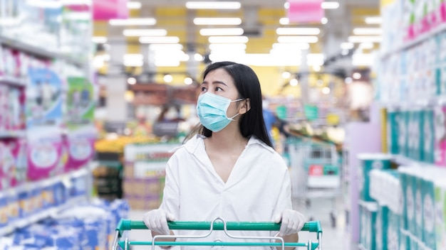 New normal woman asian wearing face mask shopping in supermarket department store