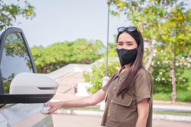 新しい通常の女性はマスクを着用してコロナウイルスcovid19を車で旅行を保護します