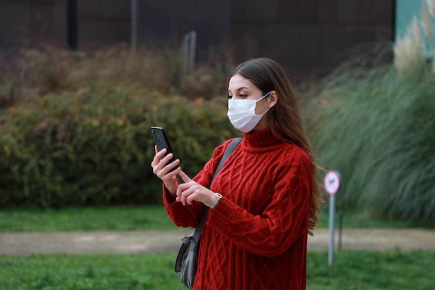 새로운 노멀. 그녀가 공원에서 걸을 때 연락처 추적의 스마트 폰 앱을 확인하는 걱정 된 여자.