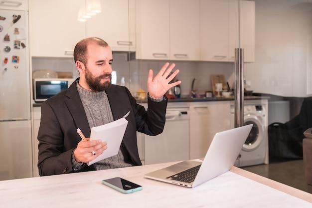 コロナウイルスのパンデミック中のニューノーマル、ビデオ通話で手を振っている自宅で働くビジネスマンの少年