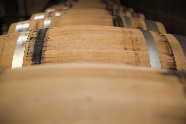 在庫の上に並んで横たわっているワインの新しいオーク樽