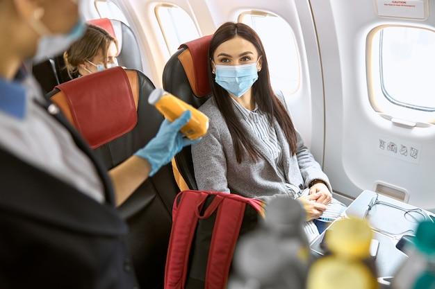 飛行機の新しい注文。スチュワーデスが彼女の飲み物を提案している間、女性はマスクに座っています