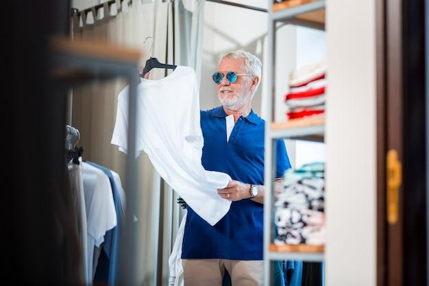 新しい衣装。好奇心旺盛な年配のお客様が白いtシャツを両手で持って精査して腰を上げる