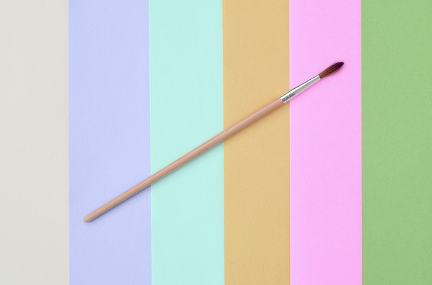 A new paint brush lie on texture of fashion pastel pink, blue, green, yellow, violet and beige colors paper